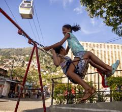 Girls swinging in public urban park