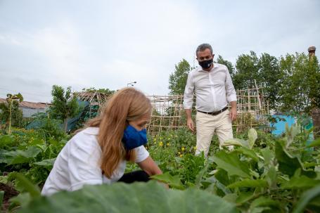 Mayor Pablo Javkin stands behind Marta Queñas, crouching, in a vegetable garden park.