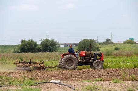 Man rides a red tractor while pulling plow in Rosario, Argentina.