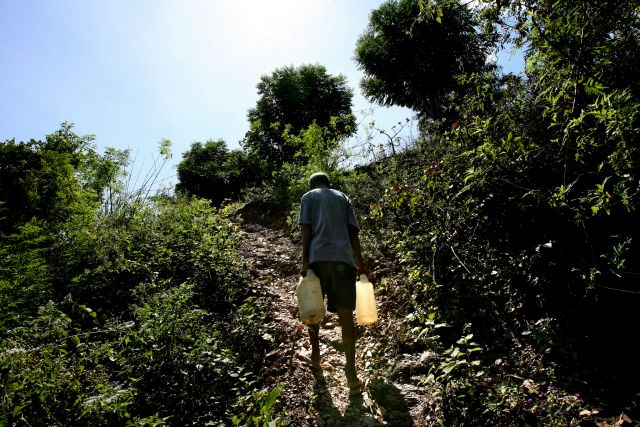 A man carries water for cooking, drinking and washing in East Timor. Flickr/Department of Foreign Affairs and Trade