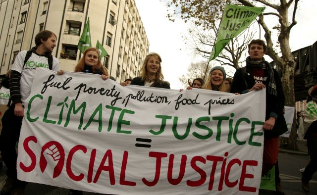"A youth group marching in Paris, with a banner that says ""climate justice = social justice."" Photo by Andreas Link/Young FoEE"