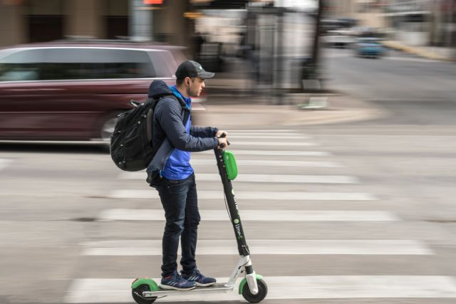 A man rides a scooter in Austin, Texas. Flickr/James Cage