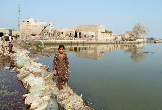 Young girl walks across a makeshift bridge in Pakistan