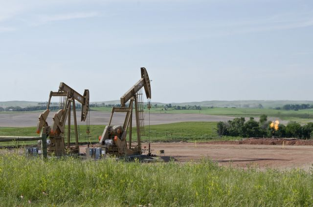 Oil wells in North Dakota with a natural gas flare in the background.