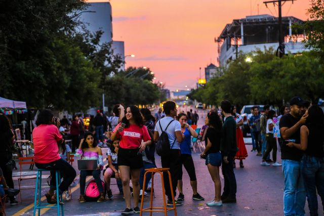 People gather in the middle of a Monterrey street during sunset