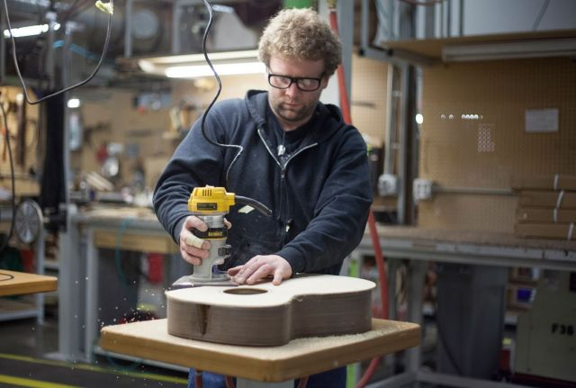 Worker routs the top of an acoustic guitar.