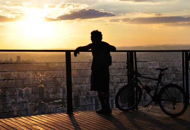 Silhouette of a person with a bicycle overlooking Belo Horizonte's skyline. Photo by Mariana Gil/WRI.