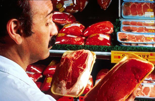 Man choosing meat in supermarket