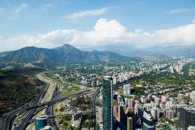 The buildings and roads of Santiago with the Andes mountains in the background.