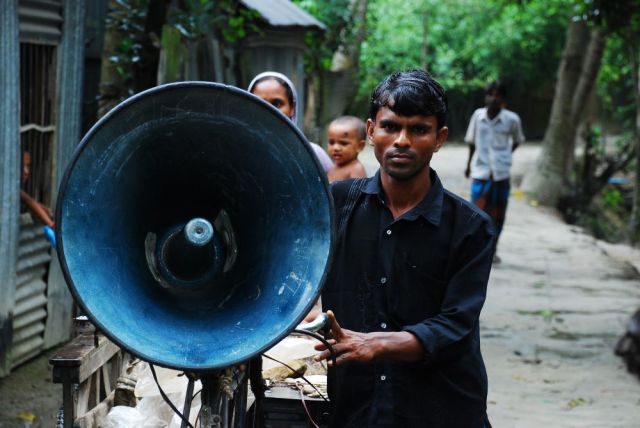 A man wheels a megaphone mounted on bicycle along a neighborhood path in Bangladesh.
