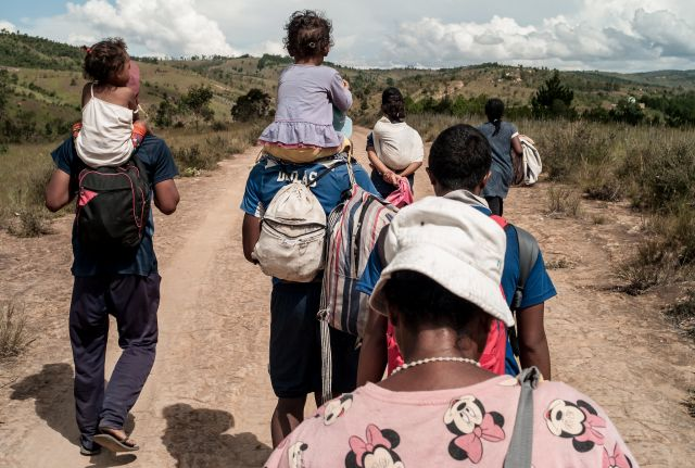 People with backpacks and small children walk on a dirt road away from Antanarivo.