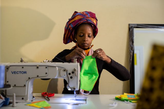 A young South African woman holds up a cloth face mask next to a sewing machine.
