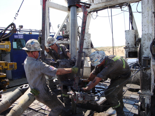 Three workers pulling machinery on an oil rig.