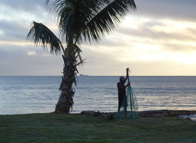 A fisherman on the beach in Fiji, handling his fishing net.