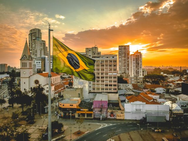 A Brazilian flag in front of a city.
