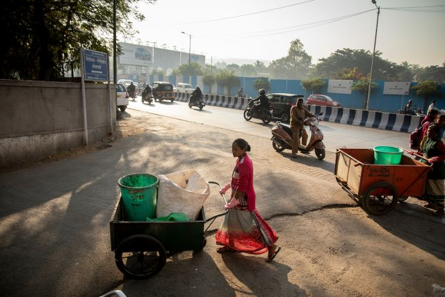 Members of a waste-pickers cooperative push collection carts along the streets of Pune, India
