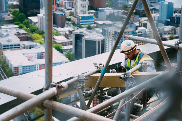 A construction worker welding pipes on a high building.