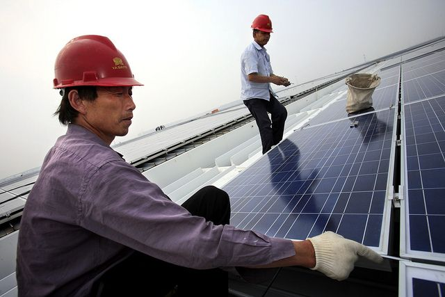 Workers install solar photovoltaic panels on roofs. (Shanghai, China) Photo by The Climate Group/Flickr.