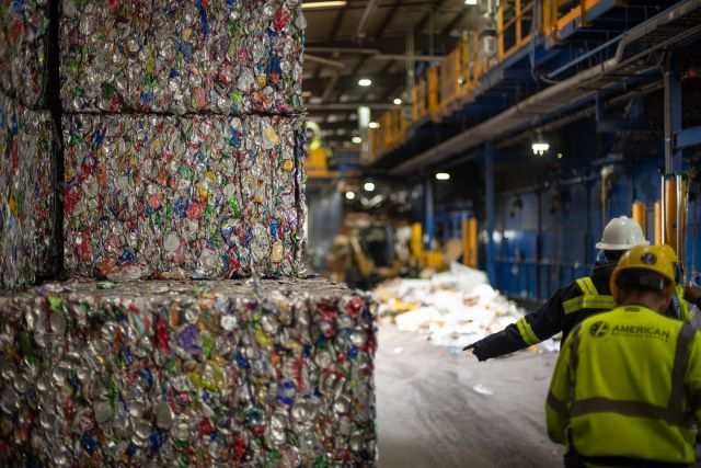 Two recycling facility workers next to bales of aluminum cans. Photo by Aaron Minnick | WRI.