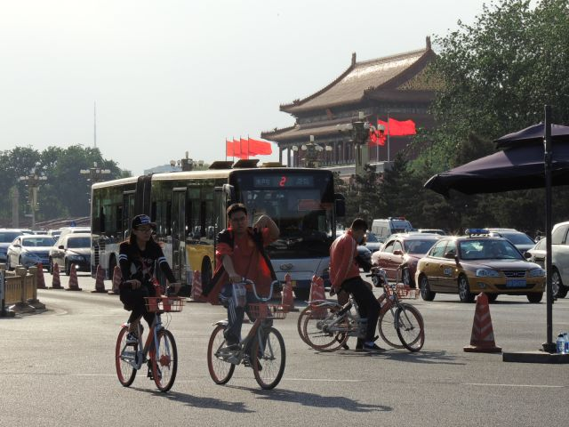 People riding bikes on a sidewalk in Beijing.