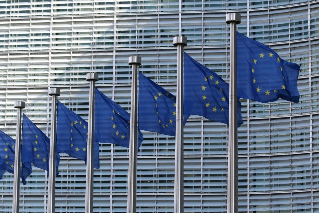 European Union flags flying in front of a building.