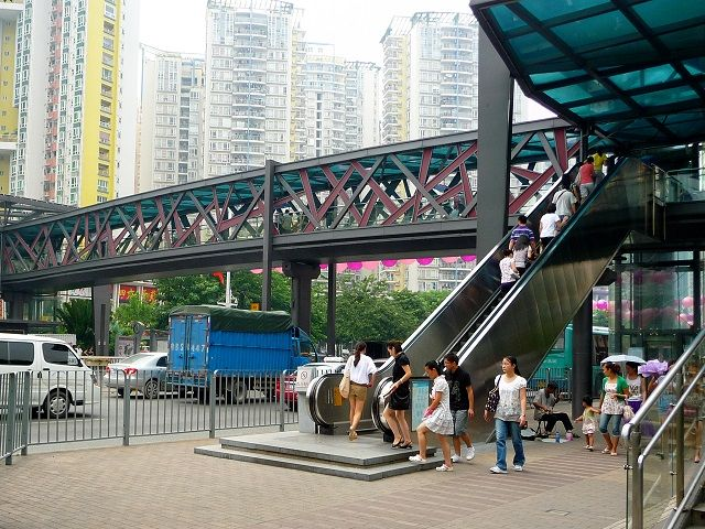 People walk on and around an outdoor escalator at a train station in Shenzhen.