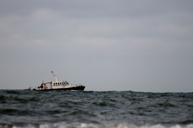A small fishing boat floating in the ocean.
