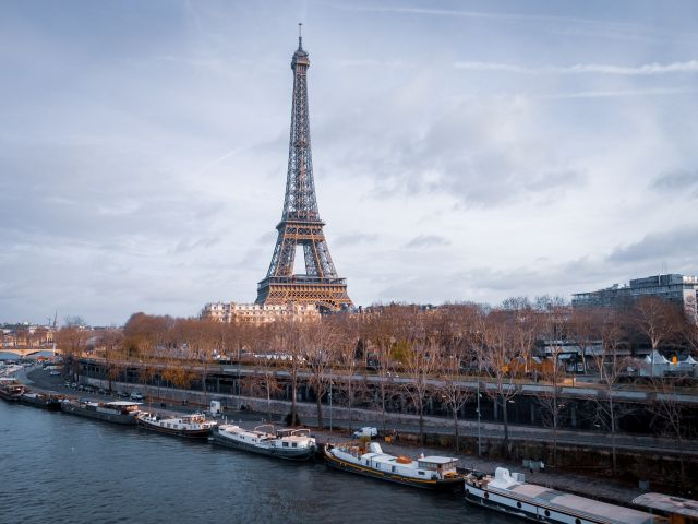A dock filled with boats with the Eiffel Tower in the background.
