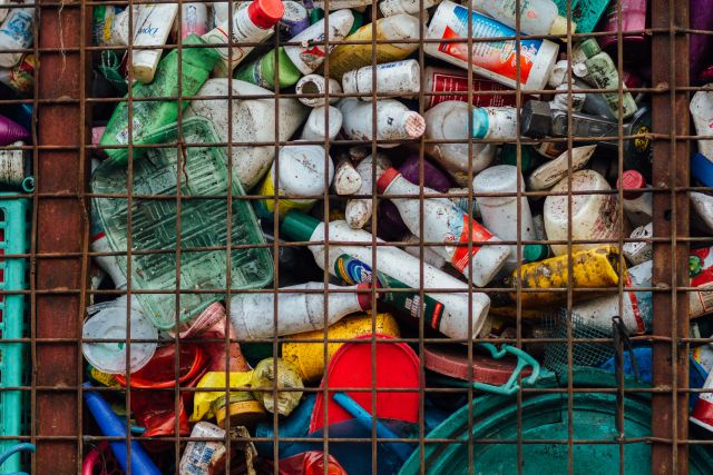 Plastic bottles and containers in metal container