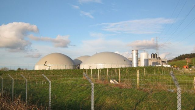 The domes and pipes of a biogas plant are visible over a low grassy field.