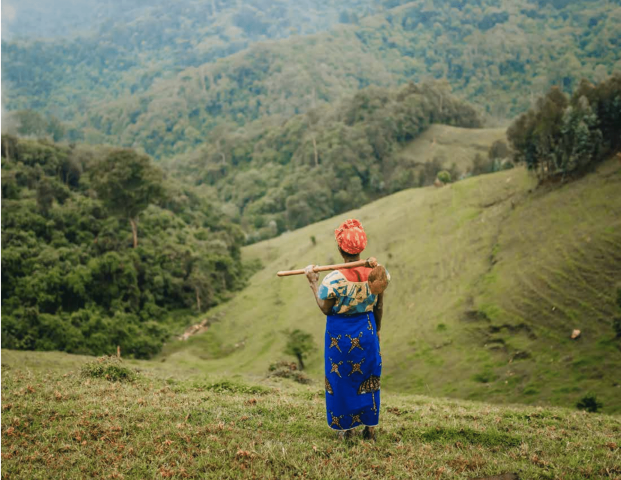 Woman stading next to a forest in Rwanda