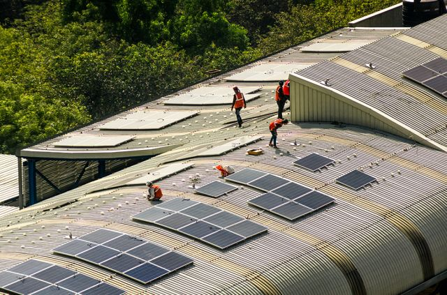 Solar panels being installed on the roof of a train station.
