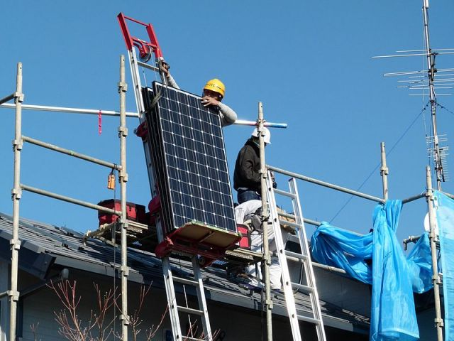 Solar installation, carefully lifting the panels at height P1000644. Photo credit: Wikipedia, 2011