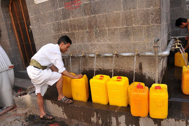 A man fills water bottles in Sanaía, Yemen Photo by Foad Al Harazi / World Bank