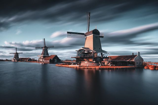 Windmills on small islands in a large body of water.