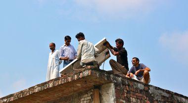 Men installing solar panel in India
