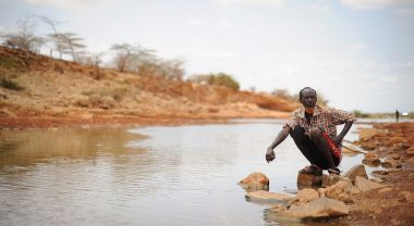 A man sits by the river in Garbahaarey town in the Gedo region of Somalia. Photo by AMISOM Public Information/Flickr.