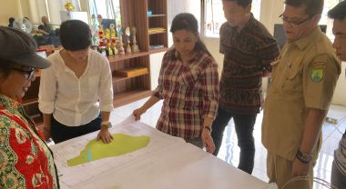 WRI Indonesia One Map team members and a government official examine local maps in the Musi Banyuasin sub-district of South Sumatra Province