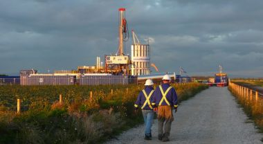 Two workers walking to a natural gas fracking operation. Photo by Justin Woolford/Flickr.