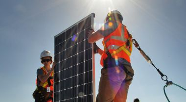 Clemson University team members install solar panels during the U.S. Department of Energy Solar Decathlon