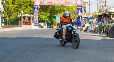 Person riding motorcycle in India during coronavirus pandemic
