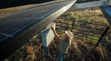 A man in a cowboy hat stands under the solar panels of his ranch's water pump. Photo by Lance Cheung/USDA.