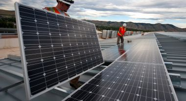 Two men install solar panels in the United States