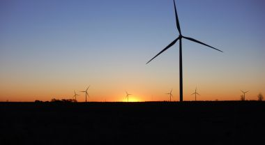 Wind turbines in the distance at sunset.