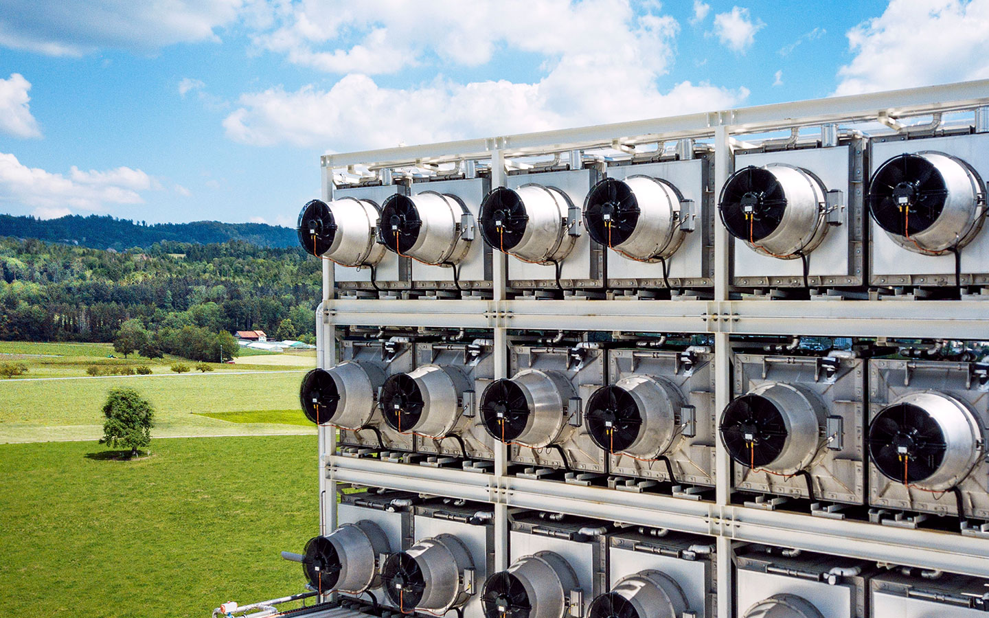 <p>Climeworks' first commercial direct air capture (DAC) plant, based in Hinwil, Switzerland. The fans draw in air, where the CO2 in that air reacts with chemicals that selectively bind it. Photo by Climeworks</p>