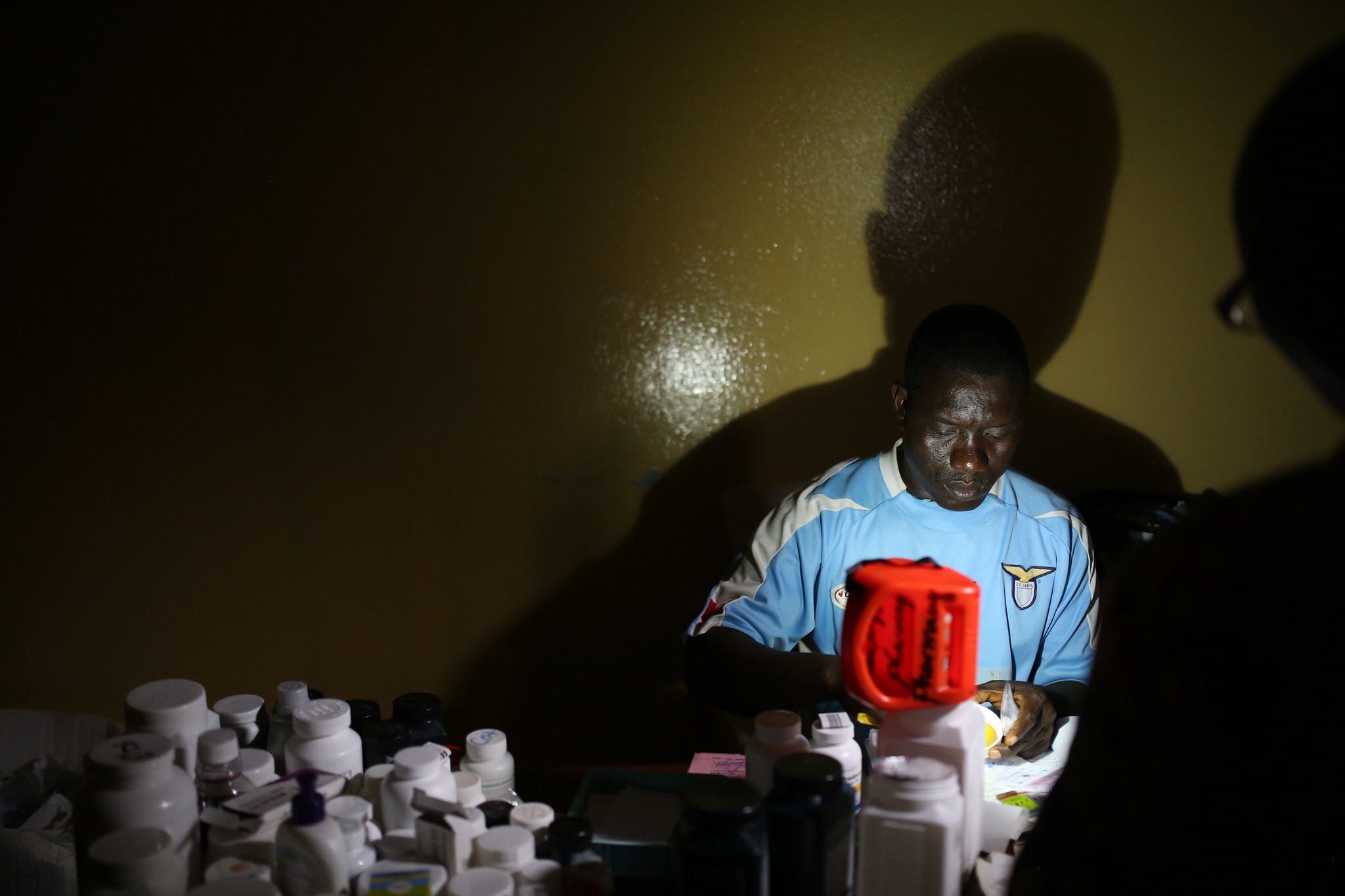 <p>A pharmacist works by flashlight at a hospital in Liberia. Photo by Dominic Chavez/World Bank.</p>