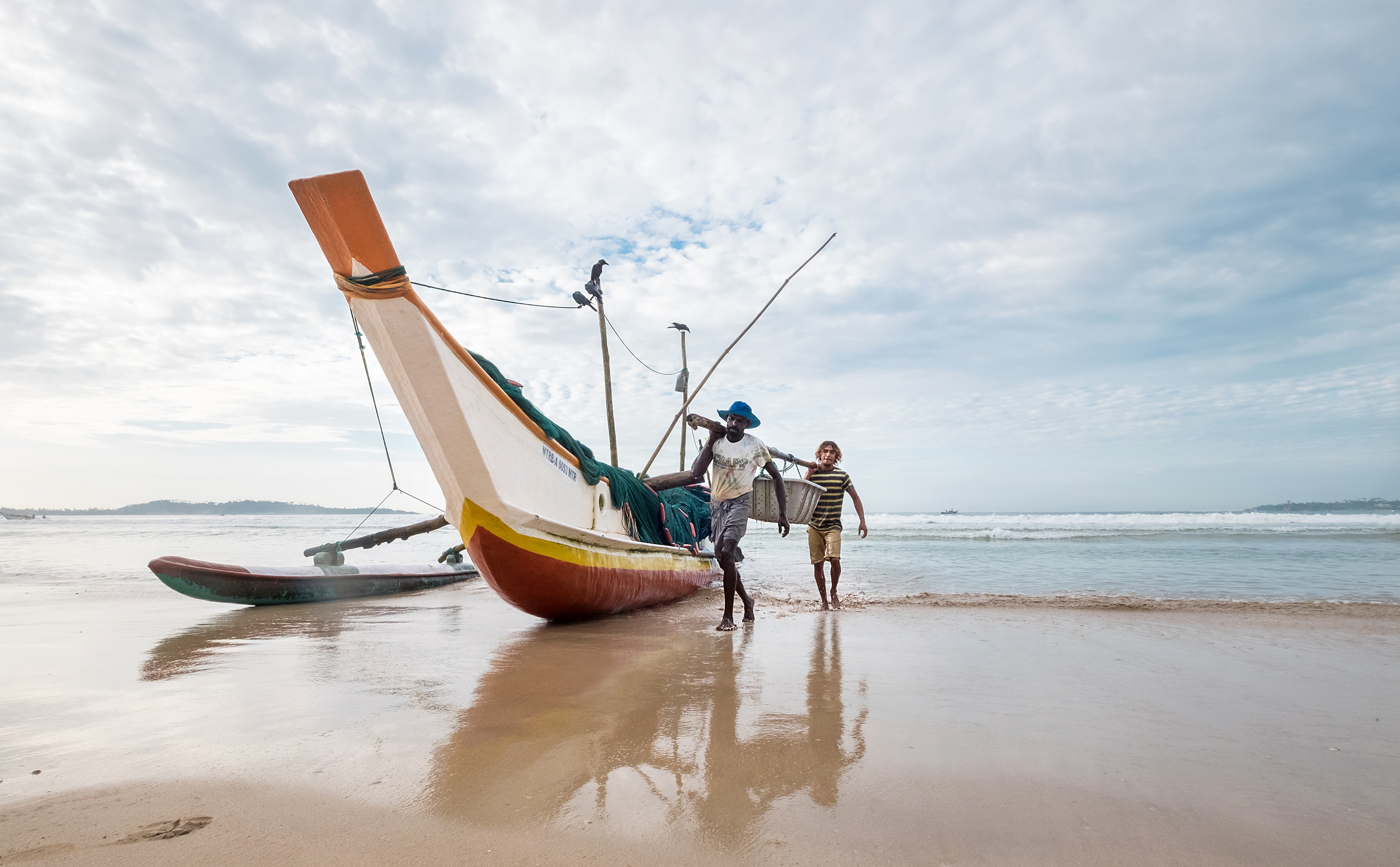 <p>Fishermen carry their catch in Weligama, Sri Lanka. Photo by iStock.com</p>